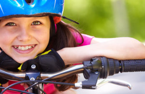 young bicyclist resting her head and hands on her handle bars